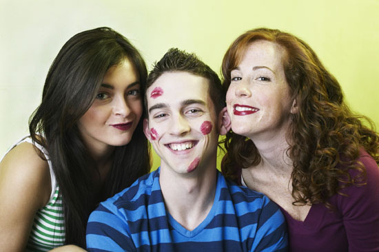 Two young women by young man with lipstick kiss marks on face, portrait