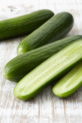 Four mini cucumbers on a wooden table top